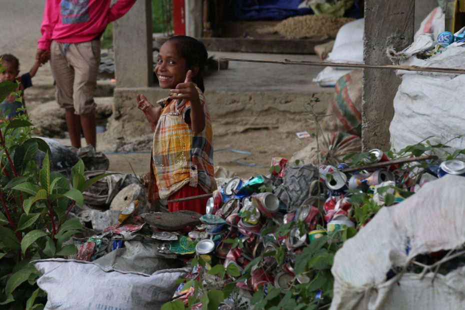 A little girl helping her family to crush and collect cans for recycling in Timor-Leste.